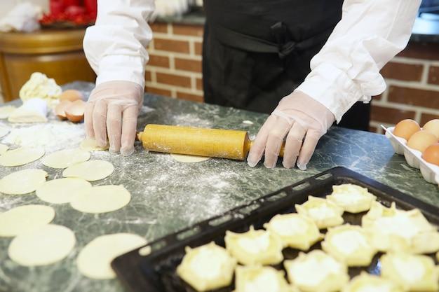 Шеф-повар-мужчина использует ингредиенты для приготовления мучных изделий на кухонном столе