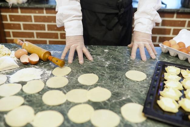 男性シェフは、台所のテーブルで小麦粉製品を準備するための材料を使用しています