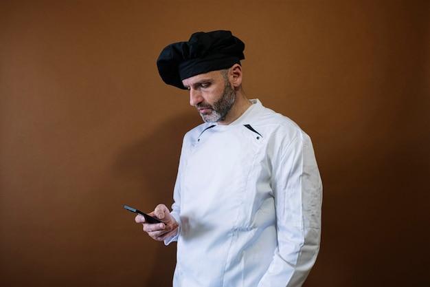 Мужчина-повар с помощью смартфона