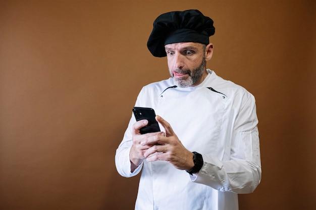 スマートフォンを使用する男性シェフ