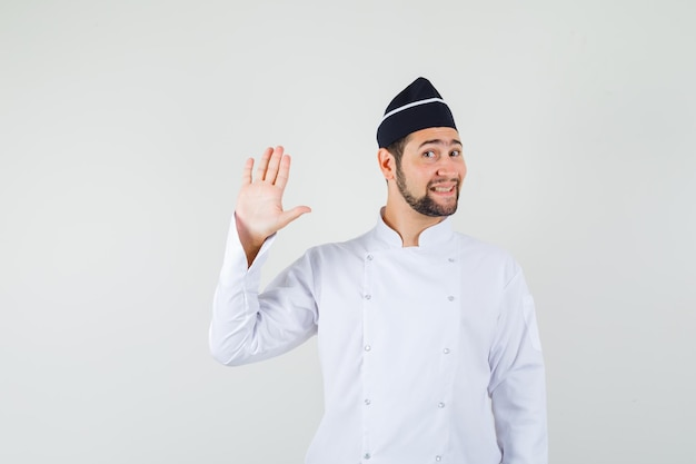 Male chef waving hand for greeting in white uniform and looking cute , front view.