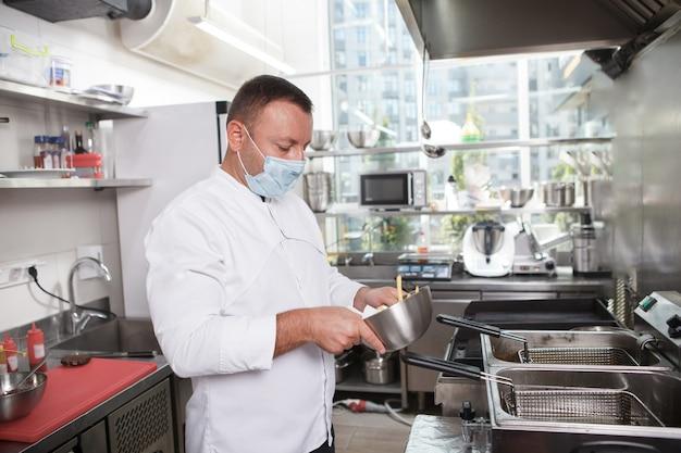 Шеф-повар-мужчина в медицинской маске во время работы на кухне ресторана, копия пространства