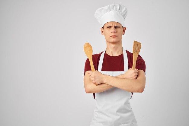 白いエプロンの台所用品を身に着けている男性シェフ料理グルメ