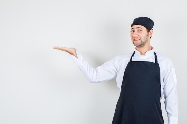 Chef maschio che accoglie o mostra qualcosa con la mano in uniforme, grembiule e dall'aspetto gentile. vista frontale.