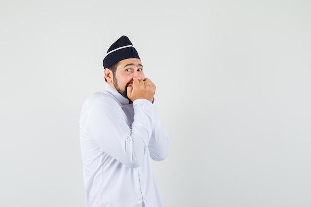 Chef maschio in uniforme bianca che unisce i pugni sulla bocca e sembra eccitato, vista frontale.