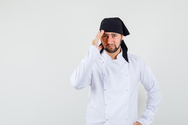 Cuoco unico maschio in uniforme bianca che ha mal di testa e sembra malato, vista frontale.
