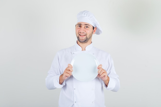 Male chef in white uniform holding empty plate and looking cheerful