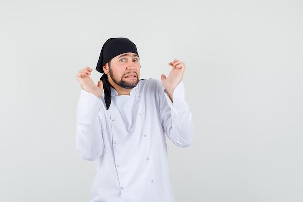 Chef maschio in uniforme bianca che si tiene per mano in gesto di resa e sembra spaventato, vista frontale.