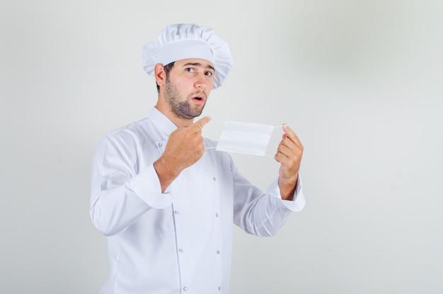Cuoco unico maschio in uniforme bianca che tiene maschera medica e sembra esitante