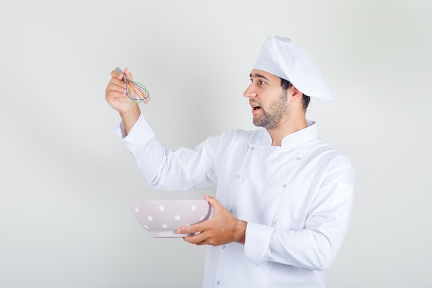 Male chef in white uniform holding whisk and bowl
