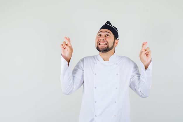 Chef maschio in uniforme bianca alzando lo sguardo con le dita incrociate e guardando allegro, vista frontale.