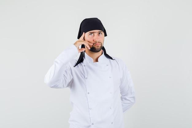 Chef maschio in uniforme bianca alzando lo sguardo con il dito sulle tempie e guardando premuroso, vista frontale.