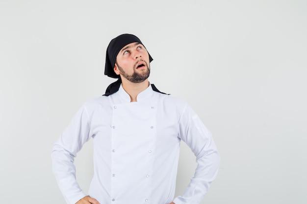 Chef maschio in uniforme bianca alzando lo sguardo con le mani sulla vita e guardando premuroso, vista frontale.