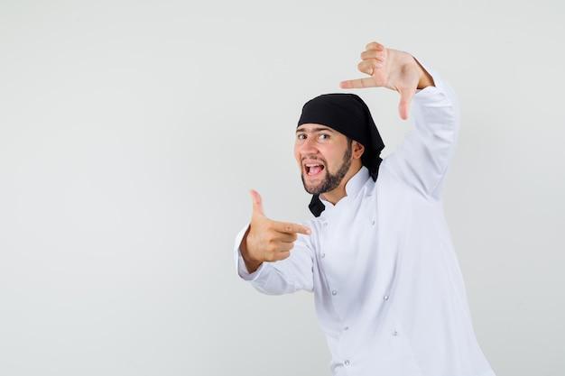 Chef maschio in uniforme bianca che fa gesto di cornice e sembra energico, vista frontale.