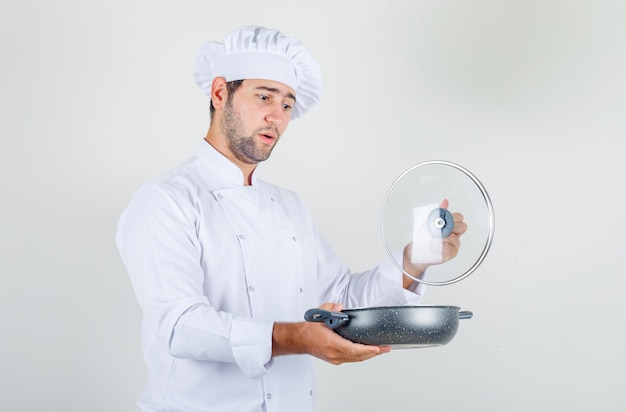 Male chef in white uniform opening glass lid of pan and looking surprised