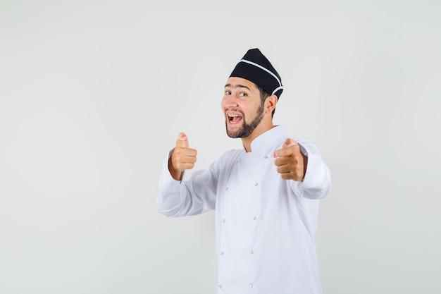 Cuoco unico maschio in uniforme bianca che indicava è venuto e sembra positivo, vista frontale.