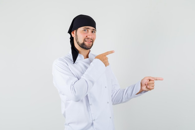 Cuoco unico maschio in uniforme bianca che punta le dita di lato e sembra positivo, vista frontale.