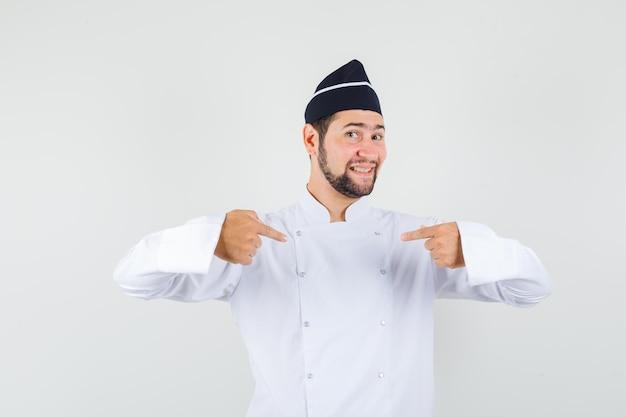 Cuoco unico maschio in uniforme bianca che indica se stesso e sembra orgoglioso, vista frontale.