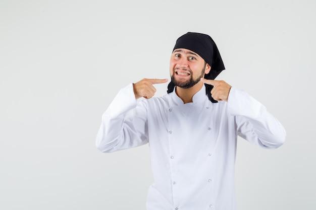 Cuoco unico maschio in uniforme bianca che indica i suoi denti, vista frontale.
