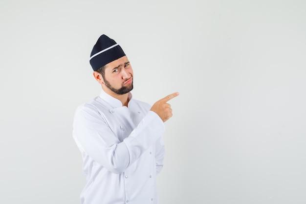 Chef maschio in uniforme bianca che punta a sinistra e sembra dispiaciuto, vista frontale. spazio per il testo