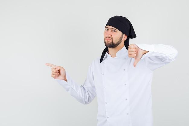 Chef maschio in uniforme bianca che punta di lato con il pollice verso il basso e sembra dispiaciuto, vista frontale.