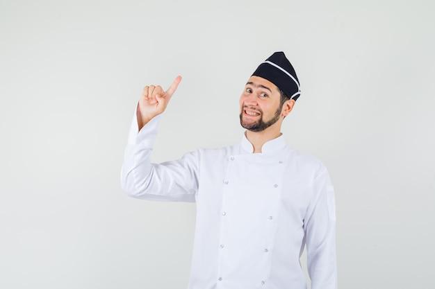 Chef maschio in uniforme bianca rivolto verso l'alto e guardando felice, vista frontale.