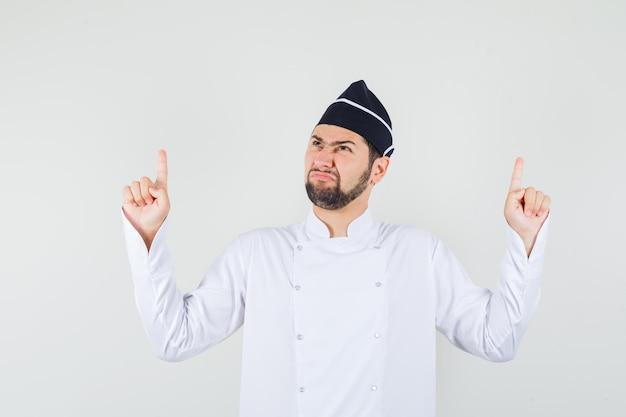 Chef maschio in uniforme bianca rivolto verso l'alto mentre accigliato, vista frontale.