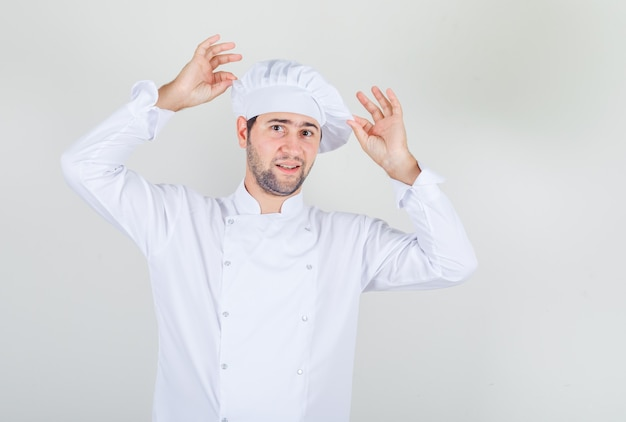 Male chef in white uniform posing while holding his hat and looking joyful