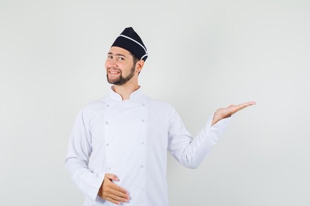 Chef maschio in uniforme bianca alzando la mano come mostrare qualcosa e sembrare contento, vista frontale.