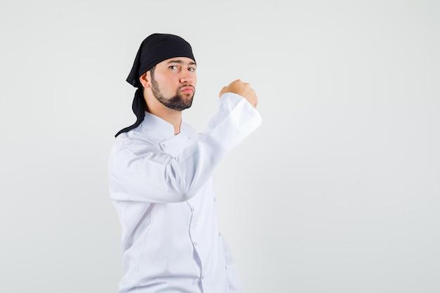 Cuoco unico maschio in uniforme bianca che mostra il pugno chiuso e sembra sicuro, vista frontale.