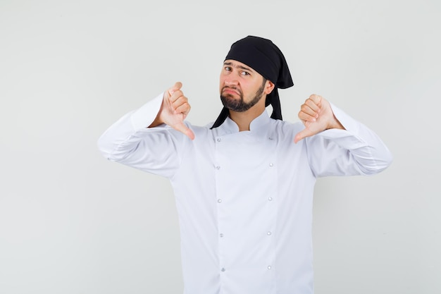 Chef maschio in uniforme bianca che mostra il doppio pollice verso il basso e sembra deluso, vista frontale.