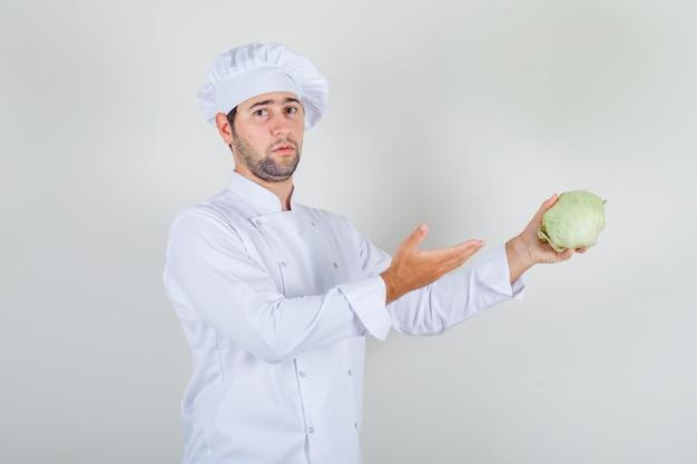 Cuoco unico maschio in uniforme bianca che mostra cavolo fresco
