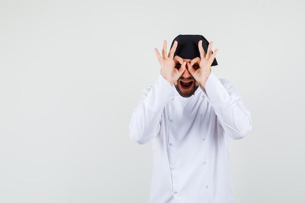 Cuoco unico maschio in uniforme bianca che mostra il gesto degli occhiali e sembra felice, vista frontale.