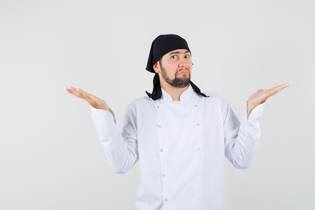 Male chef in white uniform showing helpless gesture and looking confused , front view.