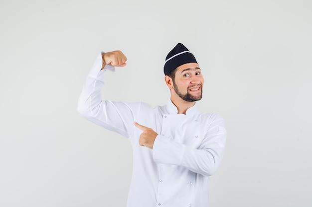 Chef maschio in uniforme bianca che mostra i muscoli del braccio e sembra fiducioso, vista frontale.