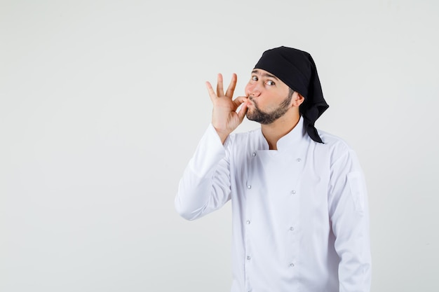 Chef maschio in uniforme bianca che mostra il gesto della zip e guarda con attenzione, vista frontale.