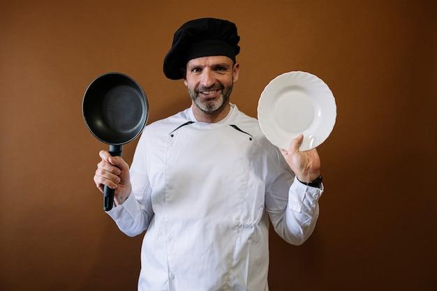 空の皿とフライパンを持つ男性シェフ