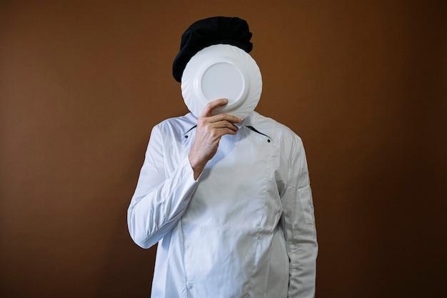 空の皿を持つ男性シェフ