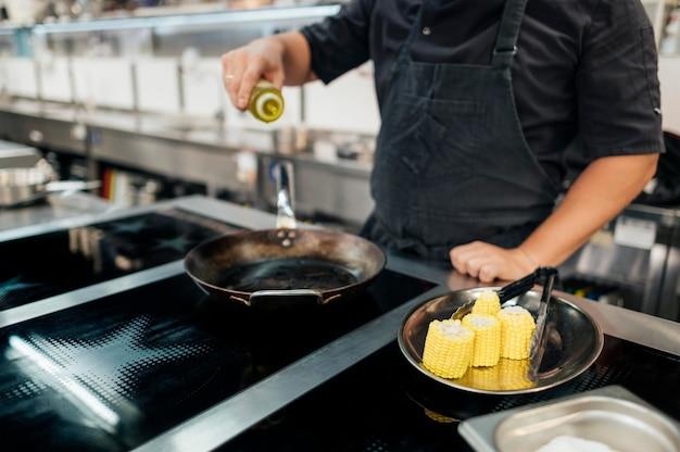鍋に油を追加するエプロンを持つ男性シェフ