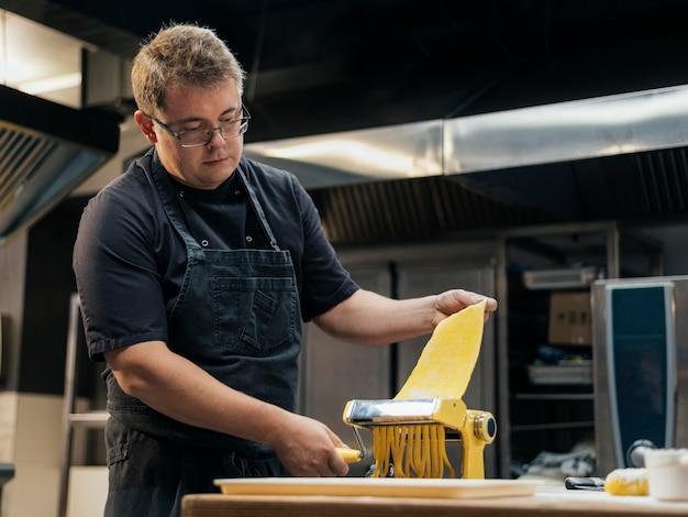 Мужской шеф-повар с фартуком, раскатывающим тесто для пасты