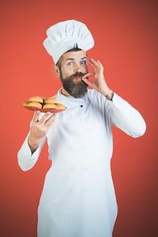 오트밀 쿠키 접시와 함께 수염과 콧수염을 가진 남성 요리사는 맛있는 수염 난 요리사 표시를 보여줍니다