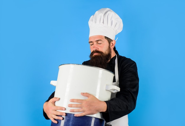 Male chef with big pot chef in cap and apron holds big saucepan food cuisine cookery and gastronomy