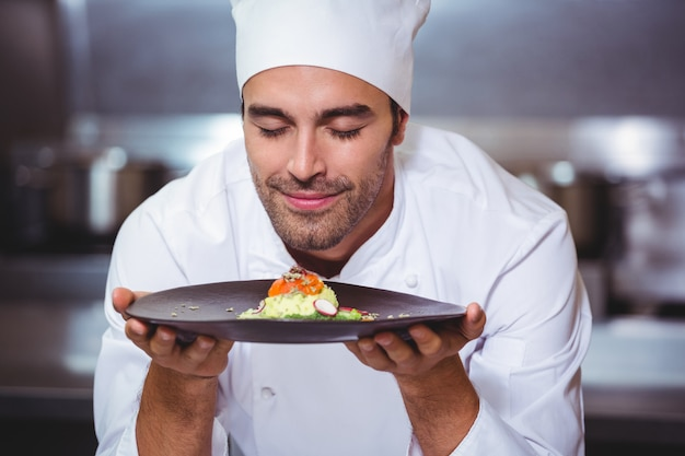 Male chef with eyes closed smelling food