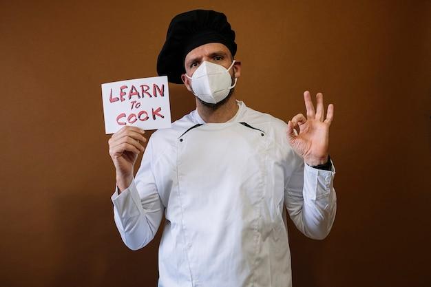 フェイスマスクと「学び、料理する」と書かれた看板を持つ男性シェフ