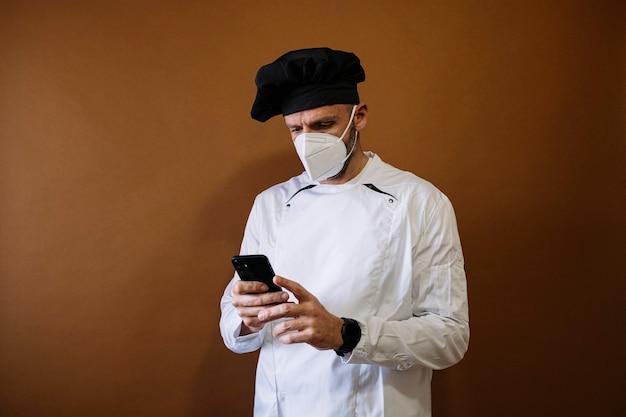 スマートフォンを使用してフェイスマスクを持つ男性シェフ