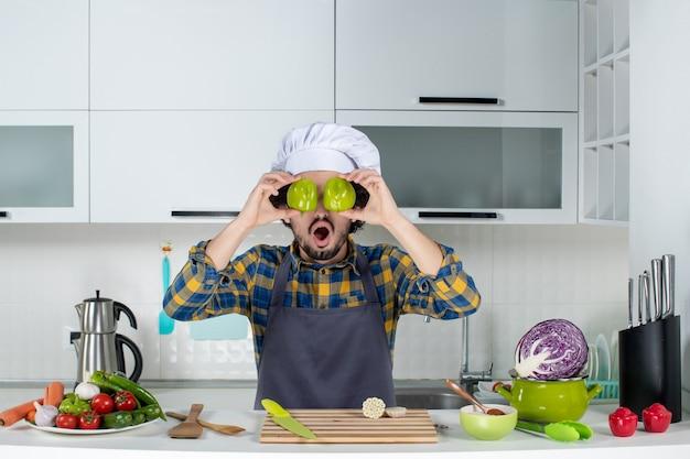新鮮な野菜とキッチンツールで調理し、白いキッチンで彼の目を覆っているカットピーマンを保持している男性シェフ