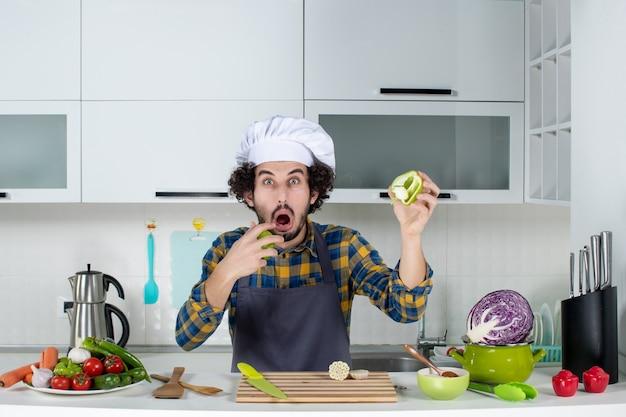 新鮮な野菜とキッチンツールで調理し、白いキッチンで驚きを感じてカットピーマンを保持している男性シェフ