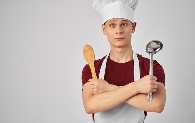 Шеф-повар-мужчина с кухонной утварью готовит еду.