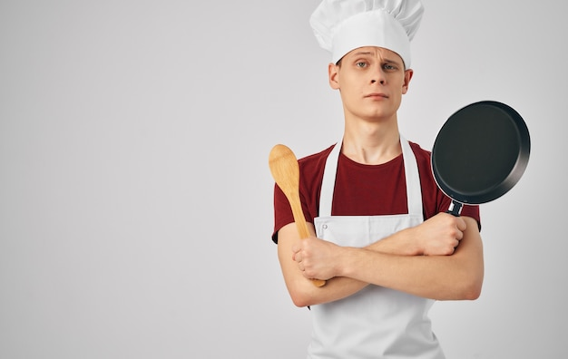 Male chef with kitchen utensils cooking food service.
