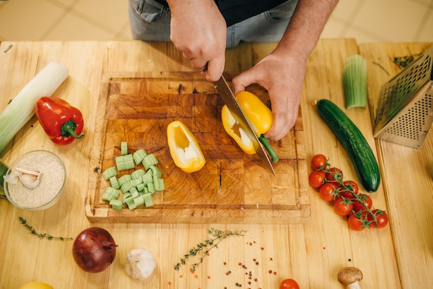 Male chef with knife cuts yellow pepper on wooden board